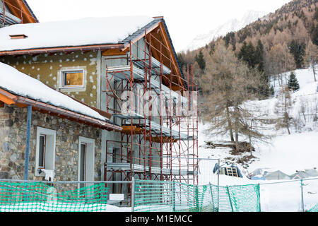 Construction of hotel or tourist apartment at ski resort in Italy, Alps - Stock Photo