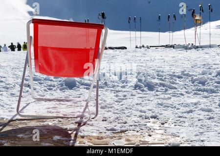 Ski poles in snow. Skiing equipment against snowy mountain in ski resort in Italy, Alps - Stock Photo