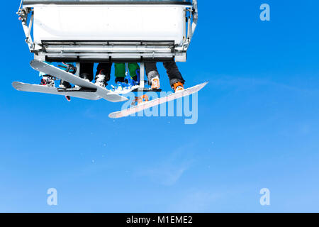 Skiers going up on the chairlift against bright blue sky- ski resort in Italy on sunny winter day - Stock Photo