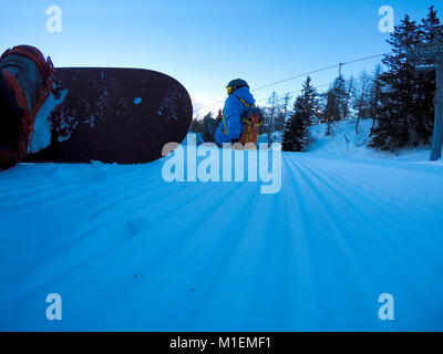 Snowboarders resting on the slope - winter sports scene. - Stock Photo