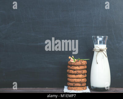 Fragrant cookies with chunks of chocolate and a jug of fresh milk on a black background - Stock Photo