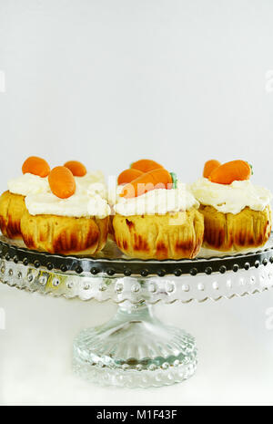 Easter cupcakes with cream cheese frosting and marzipan carrots on cake stand - Stock Photo
