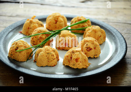 Butter mixed with dried tomatoes and herbs and shaped in small pieces to be put on bread - Stock Photo