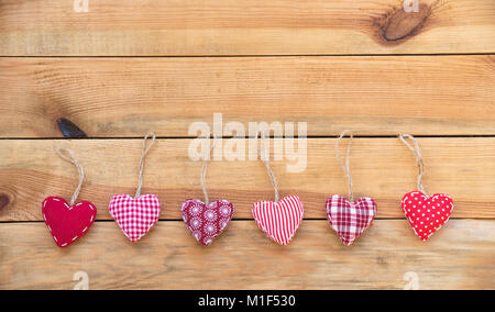 Line of red fabric hearts hanging on old wood background - Stock Photo