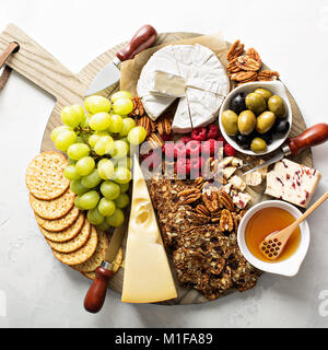 Cheese and snacks plate on white background overhead shot - Stock Photo