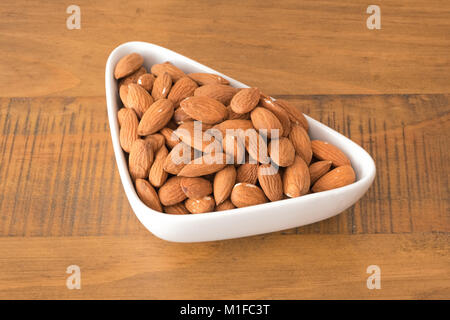 A full to the brim bowl of dried Almonds on a oak wooden table. - Stock Photo