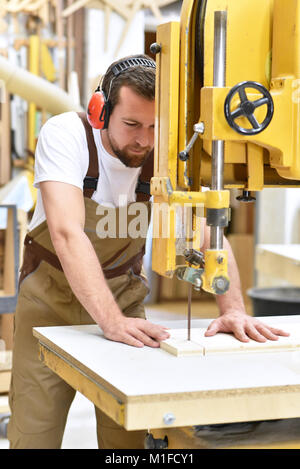 friendly carpenter with ear protectors and working clothes working on a saw in the workshop - Stock Photo