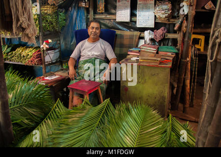 Palm seller sitting in his stall which doubles as his office, at the Mullick Ghat Flower Market in Calcutta / Kolkata, - Stock Photo
