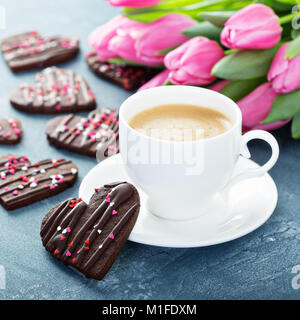 Chocolate hearts cookies with sprinkles for Valentines Day with a cup of coffee and flowers for breakfast - Stock Photo