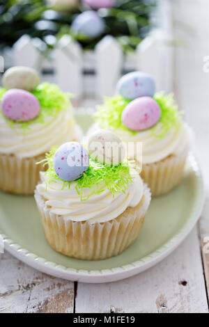 Easter vanilla cupcakes with cream cheese frosting and egg candy - Stock Photo