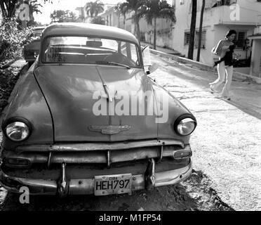 Havana, CUBA. 15th Feb, 2006. Young Cuban girl walks past one of many Cuban Maquinas, aka Yank tanks or pre 1960 - Stock Photo