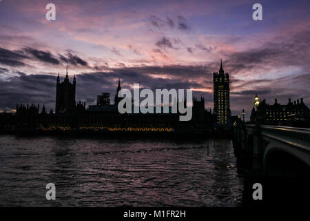 London UK. 30th January 2018. The Palace of Westminster and Elizabeth Tower are silhouetted against a colourful - Stock Photo