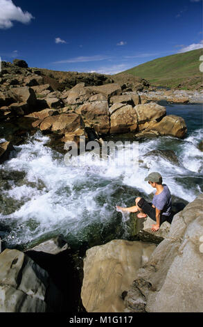 Iceland. near Borgarnes. Woman on rock by waterfall, dipping feet in water. Rapid. - Stock Photo
