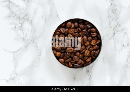 Roasted coffee beans in bowl on marble background - Stock Photo