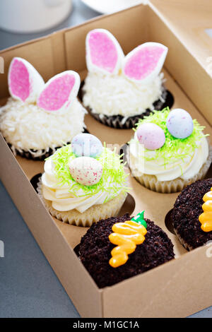 Assortment of easter cupcakes in a box with bunny ears and candy eggs - Stock Photo