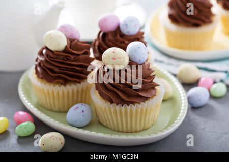 Easter vanilla cupcakes with chocolate frosting and candy eggs - Stock Photo