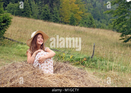 happy little girl sitting on hay - Stock Photo