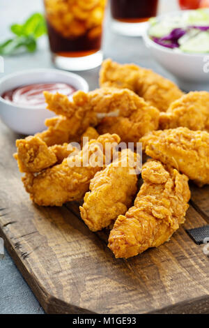 Breaded chicken tenders with ketchup, salad and soda - Stock Photo