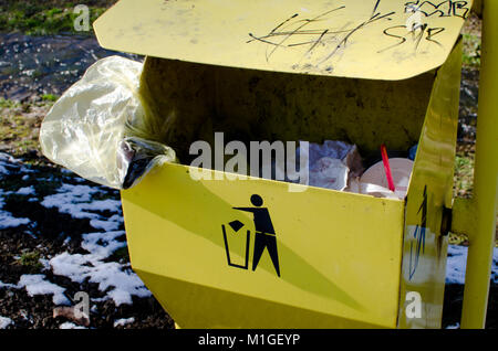 Yellow trashcan with the sign and garbage, plastic bag and bottle and straw in park - Stock Photo