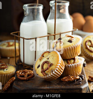Chocolate chip and pretzel muffins with milk on wooden background for dessert - Stock Photo