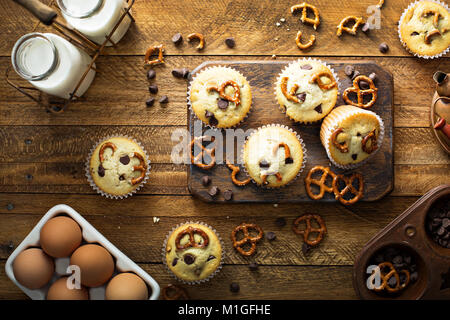 Chocolate chip and pretzel muffins with milk on wooden background for dessert overhead shot - Stock Photo