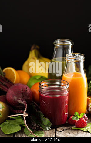 Fresh vegetable and fruit juices with beets, berries, oranges and greens - Stock Photo