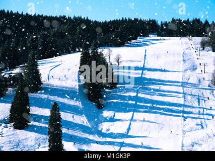 Piste ski tracks on snowy and sunny mountain side - Stock Photo