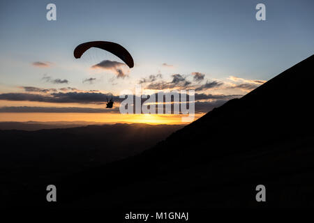 Beautiful shot of a paraglider silhouette flying over Monte Cucco (Umbria, Italy) with sunset on the background, - Stock Photo