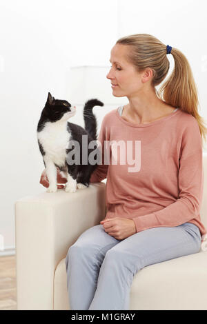 Domestic cat. Tuxedo adult and young woman sitting on a white couch. Germany - Stock Photo