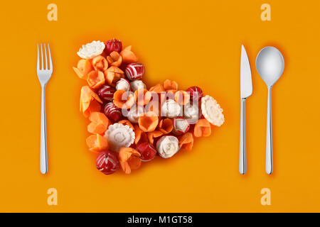 fantasy of vegetables with carrots and radishes in the shape of the heart and cutlery - Stock Photo