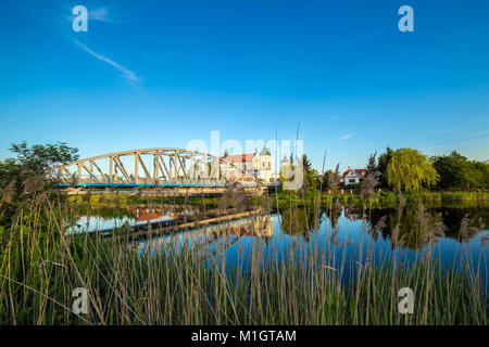 View at bridge over the Narew river and baroque Church of the Holy Trinity in Tykocin town, Podlasie, Poland - Stock Photo