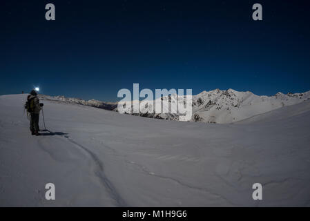 Snow on the Alps illuminated by moonlight, fisheye lens. Long exposure blurred two hikers looking at view, night - Stock Photo