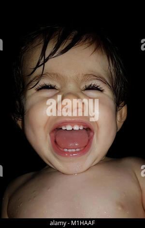 A 1-year-old little girl roaring with laughter at the time of her bath. Laughing baby. LOL - Stock Photo