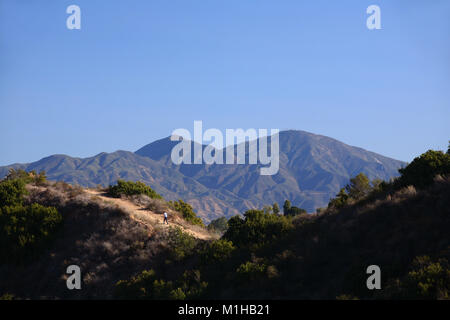 Hiker on trail in James Dilley Greenbelt preserve with view of Saddleback mountains Laguna Beach California - Stock Photo