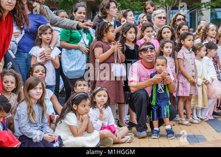 audience watches performance family Hispanic Black children girl boy - Stock Photo