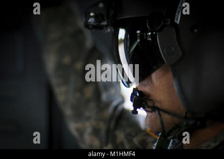 U.S. Army Chief Warrant Officer 2 Bryan Inzitari, a UH-60L Black Hawk pilot, watches from the rear of the helicopter - Stock Photo