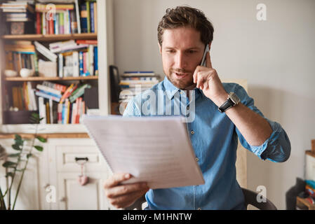 Man reading paperwork and talking on a cellphone at home - Stock Photo