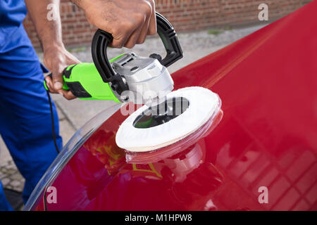 Close-up Of Person Hands Polishing Car With Orbital Polisher - Stock Photo