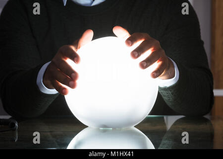Close-up Of Businessman Hands On Crystal Ball On Desk In Office