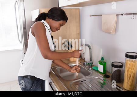 Side View Of A Young African Woman Using Plunger In Blocked Kitchen Sink - Stock Photo