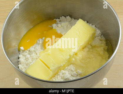 Close up of cookie or cake batter ingredients of dry flour mix, egg and softened stick of butter in stainless steel - Stock Photo