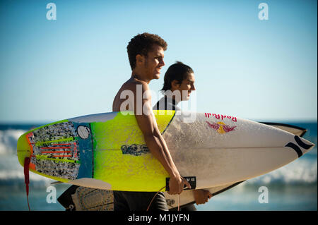 RIO DE JANEIRO - FEBRUARY 6, 2017: Young Brazilian surfers walk with their surfboards along the shore at Arpoador - Stock Photo