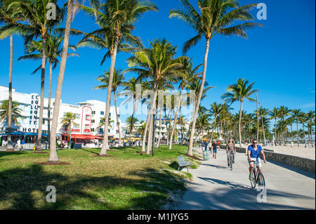 MIAMI - DECEMBER 27, 2017: Cyclists and joggers share the morning beachfront boardwalk promenade at Lummus Park - Stock Photo