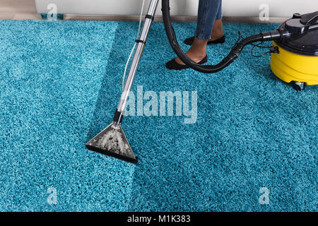 Person Using Vacuum Cleaner For Cleaning Blue Carpet At Home - Stock Photo
