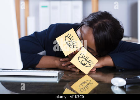 African Woman Sleeping With Eyes Drawn On Adhesive Notes At Workplace - Stock Photo