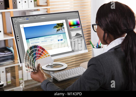 Close-up Of A African Female Designer Holding Colorful Swatch Working On Computer In Office - Stock Photo
