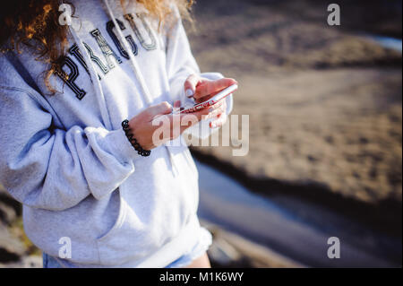 lovely young woman with curly hair, the romance of youth, a journey walk on a warm summer sunny day, uses a mobile - Stock Photo