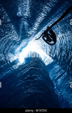 From deep inside a glacier moulin, looking straight up, the only way out is with a rope and attached ascender, used - Stock Photo