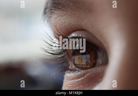 bitcoin reflecting on the screen in the eye - Stock Photo