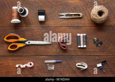 Flat lay aerial image of fashion designer items background concept.Top view sewing accessory or tailor equipment on modern rustic brown wooden at home